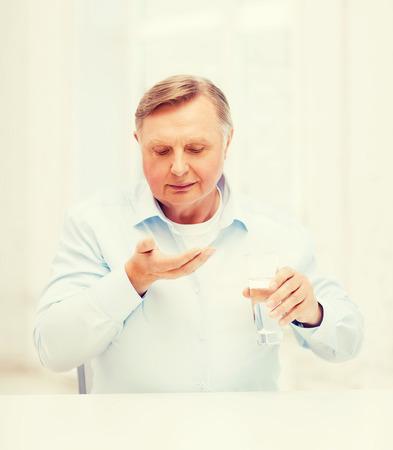 hombre viejo: salud, madicine, farmacia y ancianos concepto - anciano con pastillas y vaso de agua
