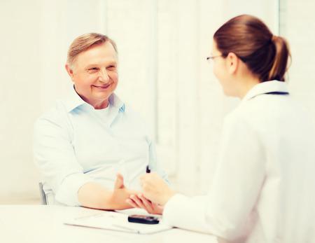Soins de santé, le concept personnes âgées et médicale - femme médecin ou une infirmière avec le patient mesure la valeur de la glycémie Banque d'images - 39595254