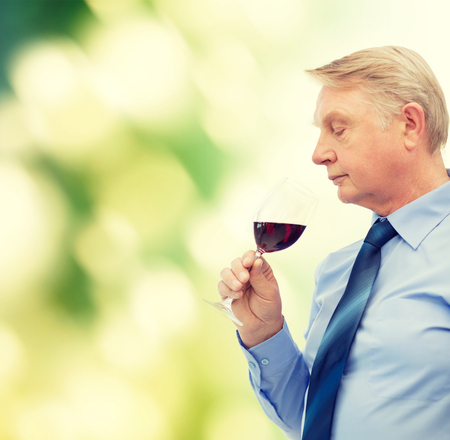smelling: alcohol and beverage concept - elderly man smelling red wine