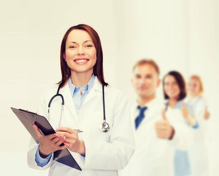 healthcare and medicine concept - smiling female doctor with clipboard and stethoscope photo