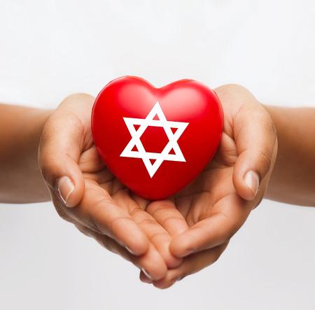 concept: religi�n, cristianismo y el concepto de la caridad - afroamericano manos femeninas celebraci�n de coraz�n rojo con la estrella de david s�mbolo