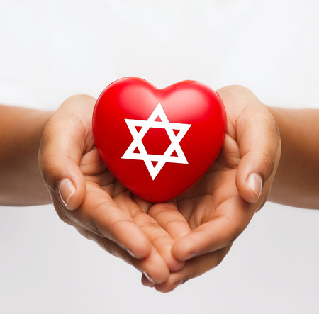 religion, christianity and charity concept - african american female hands holding red heart with star of david symbol Standard-Bild
