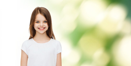 pre teens: advertising, childhood, ecology and people - smiling little girl in white blank t-shirt over green background Stock Photo