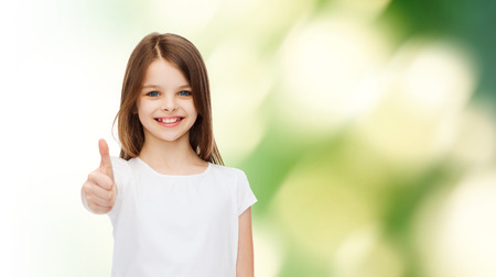 pre approval: advertising, childhood, ecology and people - smiling little girl in white blank t-shirt showing thumbs up gesture over green background