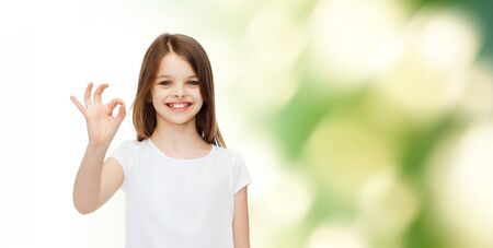advertising, childhood, gesture, ecology and people - smiling little girl in white blank t-shirt showing ok sign over green background