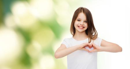 Werbung, Kindheit, Ökologie, Wohltätigkeit und Leute - lächelnde kleine Mädchen in weißen T-Shirt machen Herzform Geste über grünem Hintergrund Standard-Bild