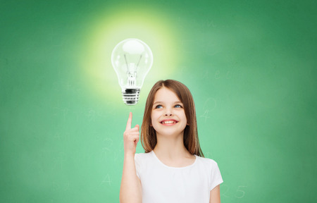 bright ideas: education, energy saving, advertising and people concept - smiling little girl in white blank t-shirt pointing finger up to light bulb over green chalk board background