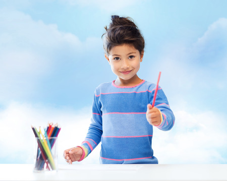 asian preteen: children, creativity and happy people concept - happy little girl drawing with coloring pencils over blue sky background