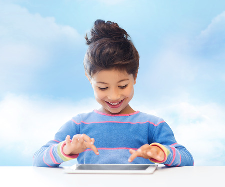 education, children, technology and people concept - happy little girl with tablet pc computer over blue sky background