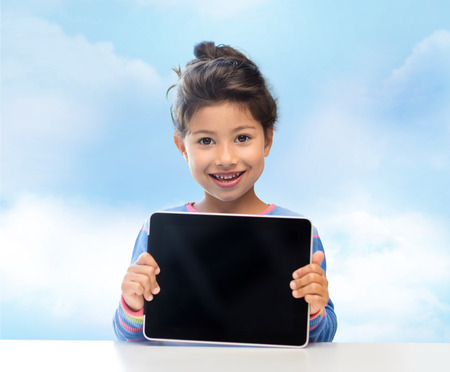 black asian: education, children, technology, advertisement and people concept - happy little girl with tablet pc computer over blue sky background Stock Photo