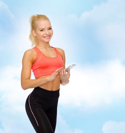 sport, fitness, technology, internet and healthcare concept - smiling sporty woman with smartphone Archivio Fotografico