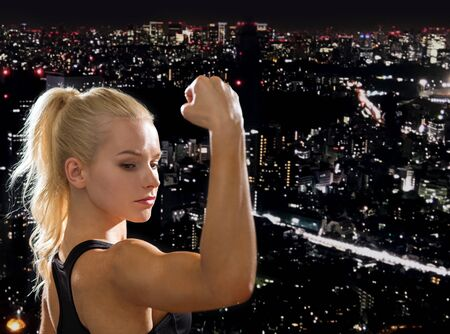 tough woman: fitness and diet concept - close up of beautiful athletic woman flexing her biceps Stock Photo