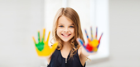 kids painted hands: education, school, art and painitng concept - smiling little student girl showing painted hands at school Stock Photo