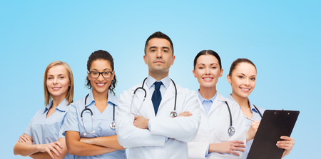 healthcare, profession, people and medicine concept - group of medics with stethoscopes over blue background photo