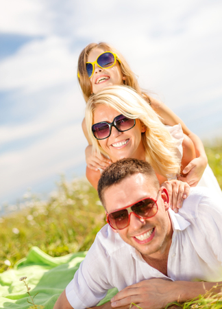 summer holidays, family, child and happy people concept - smiling family in sunglasses lying on blanket outdoors