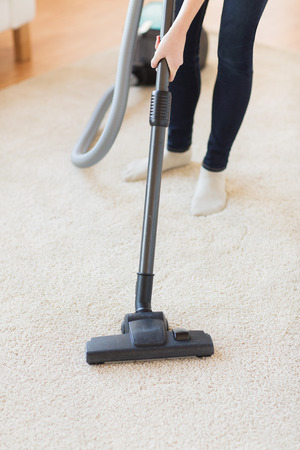 hoover: people, housework and housekeeping concept - close up of woman with legs vacuum cleaner cleaning carpet at home Stock Photo