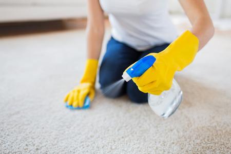 las personas, el trabajo doméstico y de limpieza concepto - cerca de la mujer en los guantes de goma con un paño y el spray derergent limpieza de alfombras en casa