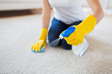 people, housework and housekeeping concept - close up of woman in rubber gloves with cloth and derergent spray cleaning carpet at home Stockfoto