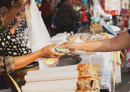 sale, retale, shopping and food concept - close up of hands giving money at street market photo