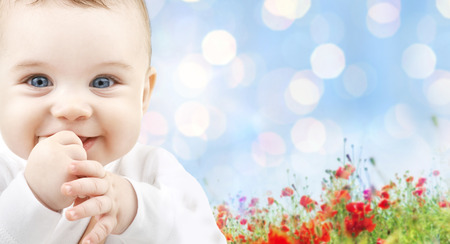 children, people, infancy and age concept - beautiful happy baby over blue lights and poppy field background Reklamní fotografie
