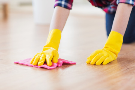 floor cloth: people, housework and housekeeping concept - close up of woman in rubber glover with cloth cleaning floor at home Stock Photo