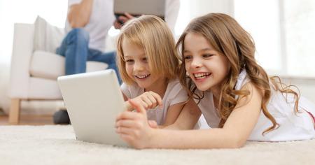家族、子供、技術とホームのコンセプト - タブレット pc コンピューターとラップトップで背中に両親と妹を笑顔