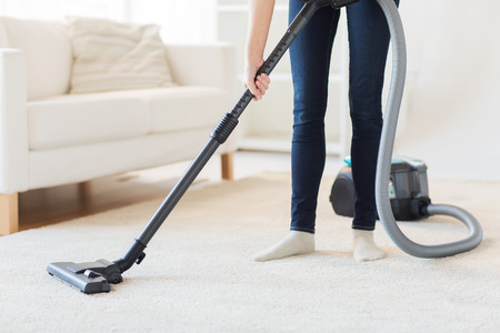 people, housework and housekeeping concept - close up of woman with legs vacuum cleaner cleaning carpet at home Foto de archivo