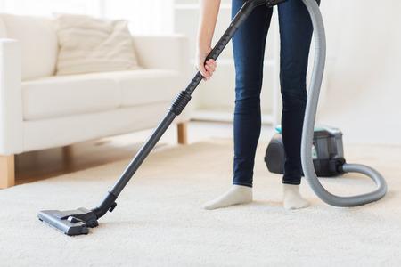 personal de limpieza: las personas, el trabajo dom�stico y de limpieza concepto - cerca de la mujer con las piernas aspiradora limpieza de alfombras en casa Foto de archivo