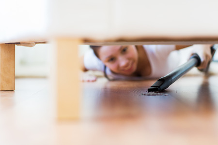 people, housework and housekeeping concept - close up of happy woman with vacuum cleaner cleaning floor under couch at home