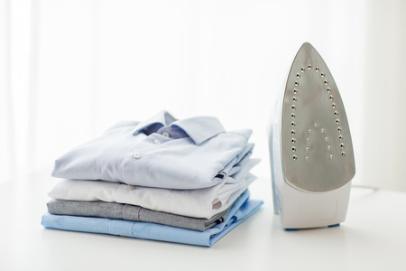 pile of clothes: ironing, clothes, housework and objects concept - close up of iron and clothes on table at home