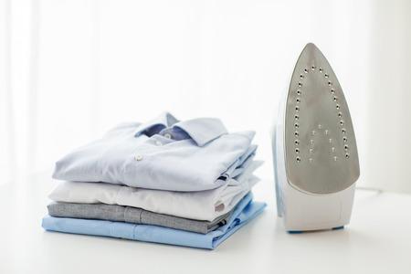 lavanderia: plancha, ropa, tareas domésticas y objetos concepto - cerca de hierro y ropa en la mesa en casa