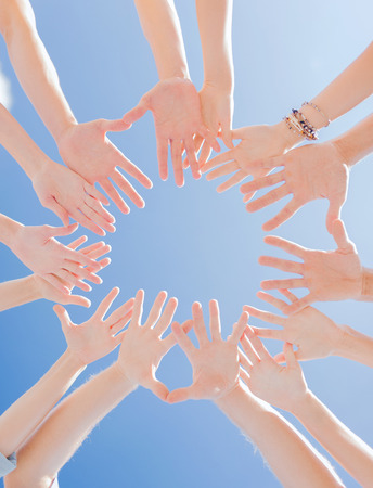 charitable: togetherness, team, union, people and gesture concept - close up of many hands over blue sky background