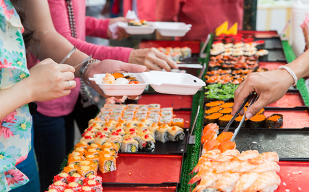 multiple choice: cooking, asian kitchen, sale and food concept - close up of hands with tongs taking sushi at street market Stock Photo