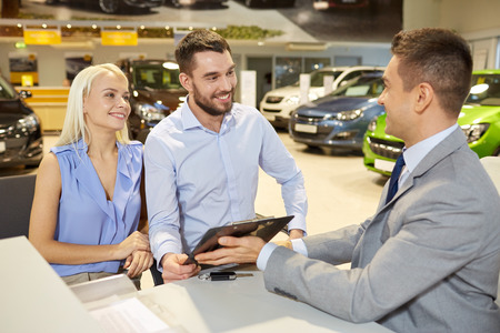 car loans: auto business, sale and people concept - happy couple with dealer buying car in auto show or salon