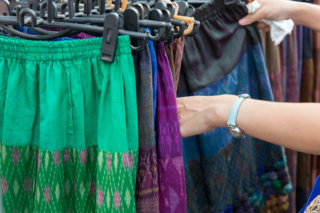 skirts: sale, retail, shopping and clothing concept - close up of hands choosing skirts at street market
