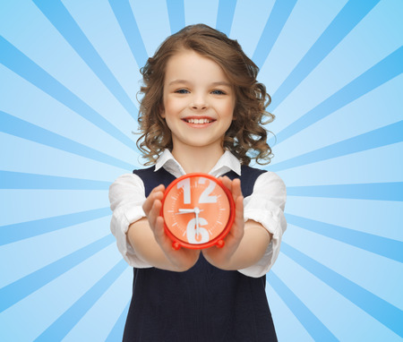 punctuality: people, childhood, time and punctuality concept - happy girl with alarm clock over blue burst rays background
