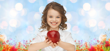 over eating: people, children, healthy eating, summer and food concept- happy girl holding red apple over blue sky and poppies field n background Stock Photo