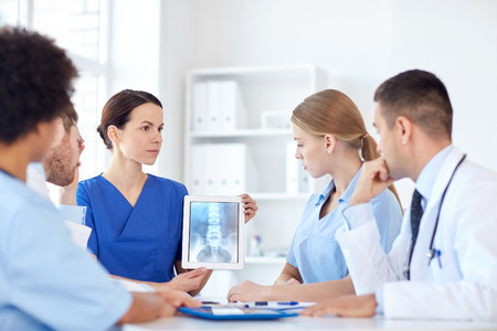 profession, people, surgery, radiology and medicine concept - group of doctors with x-ray on tablet pc computer screen meeting at medical office Stock Photo