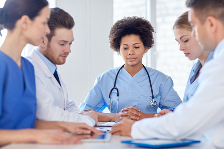 hospital, profession, people and medicine concept - group of happy doctors meeting at medical office Stockfoto