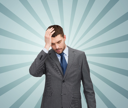 displeased businessman: business, fail and crisis concept - young businessman having headache over blue burst rays background Stock Photo