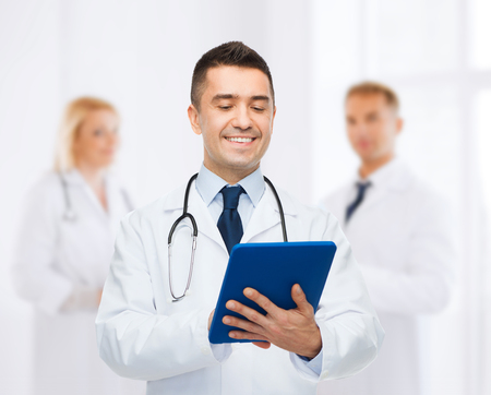 medics: healthcare, profession, people and medicine concept - smiling male doctor in white coat with tablet pc over group of medics at hospital background Stock Photo
