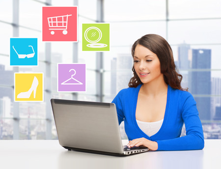business, people and technology concept - smiling businesswoman or student with laptop computer shopping online in office