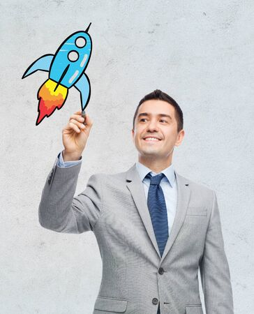 gray suit: business startup, development, management and people concept - happy smiling businessman in suit drawing rocket doodle with marker over gray background