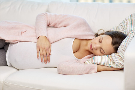 lying on stomach: pregnancy, rest, people and expectation concept - happy pregnant woman sleeping on sofa at home