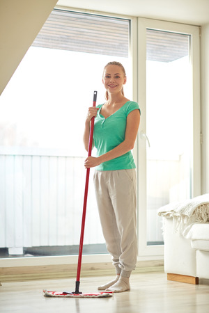 swab: people, housework and housekeeping concept - happy woman with mop cleaning floor at home