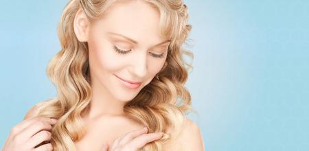 schoonheid, mensen, haarverzorging en gezondheidsconcept - mooi jong vrouwengezicht met lang golvend haar over blauwe achtergrond