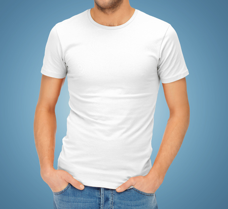 clothing design, advertisement, fashion and people concept - close up of ma in blank white t-shirt over blue background Stock Photo