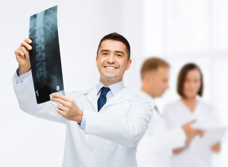 orthopedist: healthcare, rontgen, people and medicine concept - smiling male doctor in white coat with x-ray over group of medics at hospital background Stock Photo