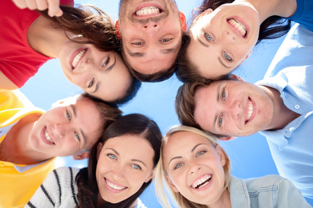 beautiful girl face: friendship, summer vacation, holidays and people concept - group of smiling friends standing in circle over blue sky