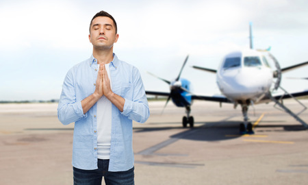 man flying: faith in god, hope and people concept - happy man with closed eyes praying over airplane on runway background